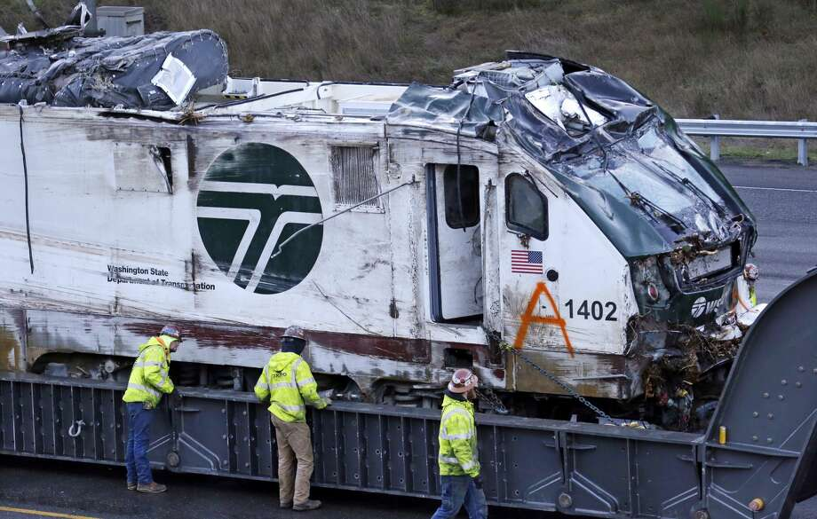 The engine from an Amtrak train crash onto Interstate 5 on Monday, is checked by workers before being transported away from the scene, Wednesday, Dec. 20, 2017, in DuPont, Wash.  Federal investigators in the deadly train wreck want to know whether the engineer was distracted by a second person in his cab as his train hurtled into a curve at more than twice the speed limit.  The train took a 30 mph curve at 80 mph and plunged off an overpass, sending rail cars plummeting onto a busy highway south of Seattle.  (AP Photo/Elaine Thompson) Photo: Elaine Thompson/AP