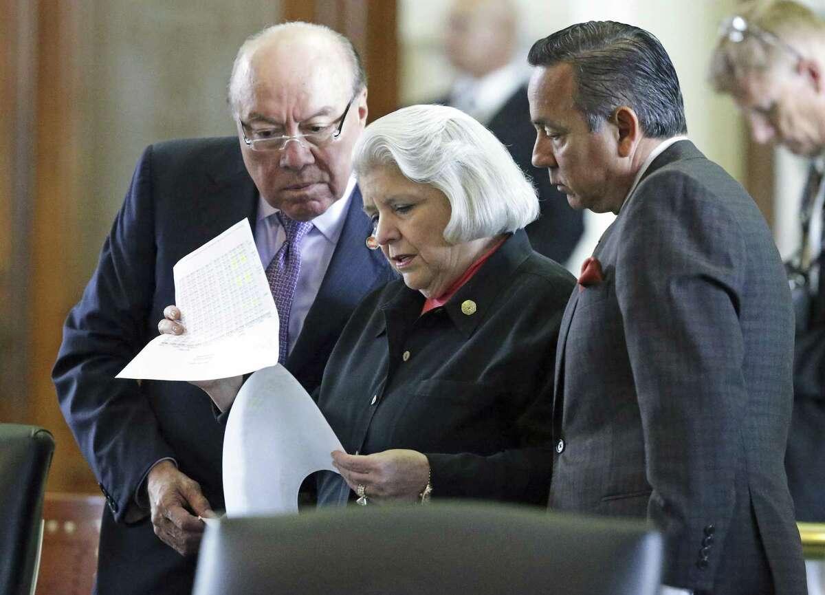 Senator Judith Zaffirini goes through pages of legislation with Senaotr Juan Hinojosa (left) and Senator Carlos Uresti on the second day of the special legislative session on July 18, 2017.
