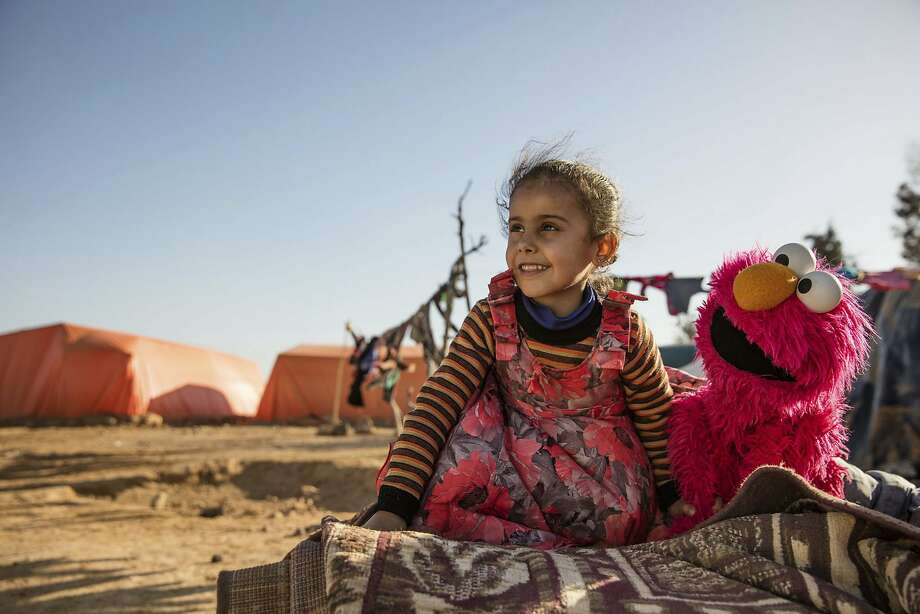 """In this Feb. 2017 photo Photo courtesy of Ryan Heffernan and Sesame Workshop, a young girl engages with Sesame Street caricature Elmo at an informal tented settlement near Mafraq,Jordan. The John D. and Catherine T. MacArthur Foundation announced Wednesday, Dec. 20, 2017, that Sesame Workshop and International Rescue Committee will get a $100 million grant from a Chicago-based foundation. for a joint program that will include home visits focused on early learning, child development centers and a local version of """"Sesame Street."""" (Ryan Heffernan/Sesame Workshop via AP) Photo: Ryan Heffernan, Associated Press"""
