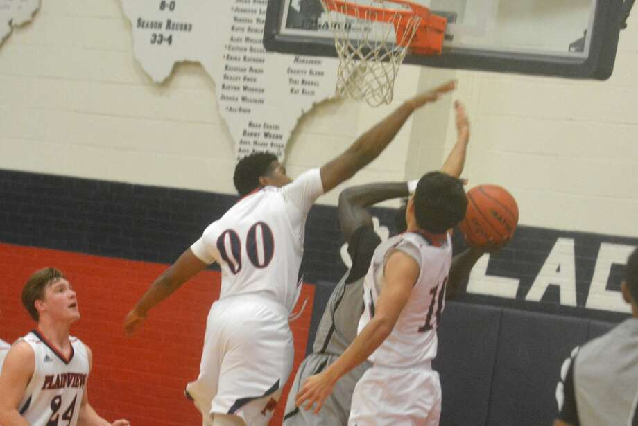 Plainview's Joseph Guy, 00, and Adrian Hinojosa, 10, defend against an Odessa Permian player in a game last week. The Bulldogs opened their District 3-5A campaign Tuesday night with an 82-39 shellacking of Dumas. Photo: Skip Leon/Plainview Herald
