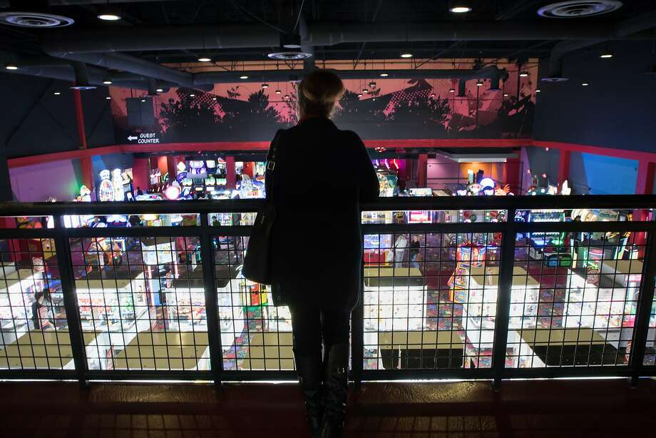 Yolanda Posadas looks out over the arcade games while waiting for her kids at Round1 at the Sunvalley mall. Photo: Paul Kuroda, Special To The Chronicle