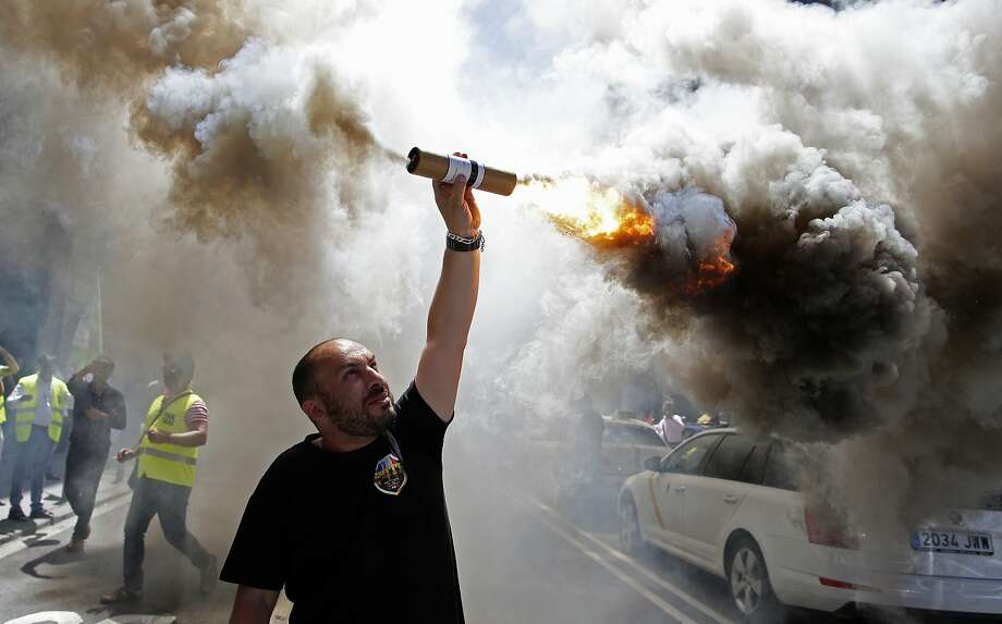 FILE - In this June 29, 2017 file photo, a protestor burns a flare during a taxi strike and protest against companies such as Uber and Cabify in Barcelona, Spain. The European Union's top court has ruled on Wednesday Dec. 20, 2017 that ride-hailing service Uber should be regulated like a taxi company, a decision that could change the way it functions across the continent. (AP Photo/Manu Fernandez, File) Photo: Manu Fernandez, Associated Press