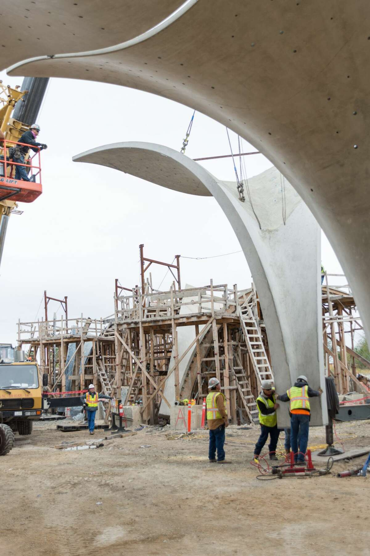 Workers piece together the last petal structure at Confluence Park on Dec. 5, 2017.