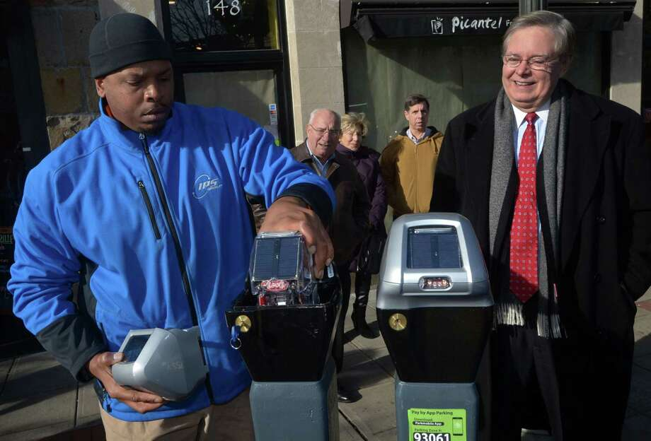 IPS Group Field Technician Alexander Miles replaces the last of the old coin-op parking meters on Bedford Street with new digital meters that accept credit cards as Mayor David Martin announce the installation of the new parking meters Wednesday, December 20, 2017, in downtown Stamford, Conn. Over 70 meters were replaced on Bedford Street. Photo: Erik Trautmann / Hearst Connecticut Media / Norwalk Hour
