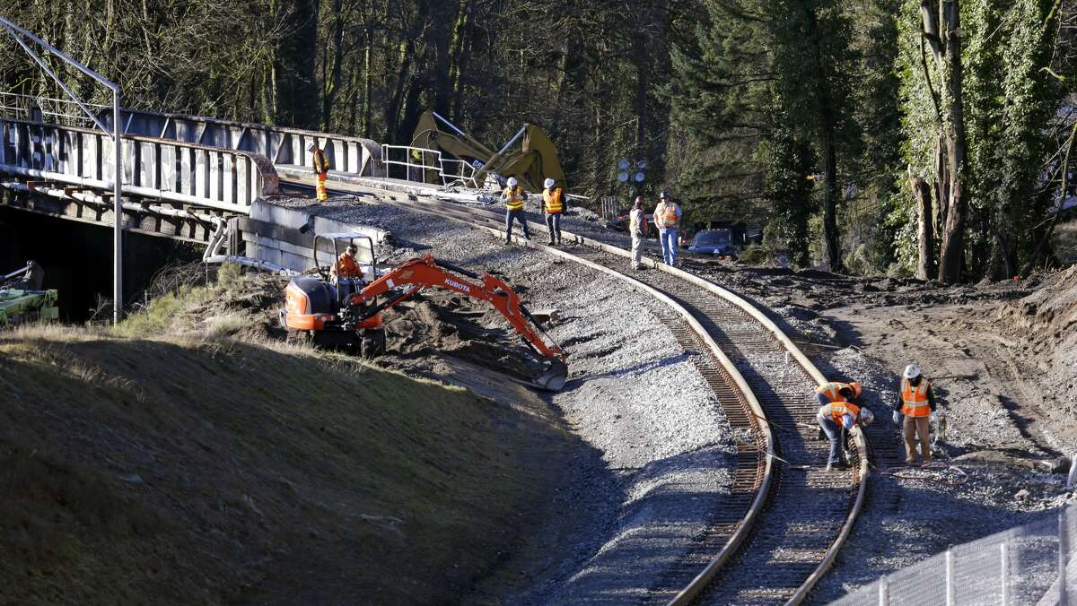 People work at the curve leading to the railroad bridge where an Amtrak train derailed onto Interstate 5 two days earlier Wednesday, Dec. 20, 2017, in DuPont, Wash. The Amtrak train that careened off the overpass south of Seattle, killing at least three people, was hurtling 50 mph over the speed limit when it jumped the track, federal investigators say, when it derailed along a curve, spilling railcars onto the highway below. (AP Photo/Elaine Thompson)
