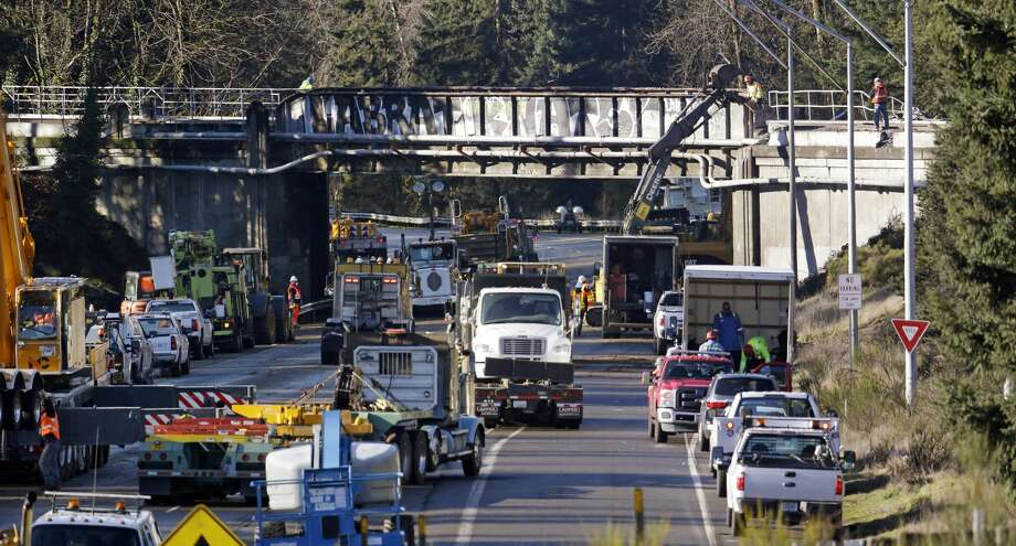 Vehicles fill the highway at the scene of an Amtrak train crash onto Interstate 5 from the railroad bridge above two days earlier Wednesday, Dec. 20, 2017, in DuPont, Wash. The Amtrak train that careened off the overpass south of Seattle, killing at least three people, was hurtling 50 mph over the speed limit when it jumped the track, federal investigators say, when it derailed along a curve, spilling railcars onto the highway below. (AP Photo/Elaine Thompson) Photo: Elaine Thompson/AP