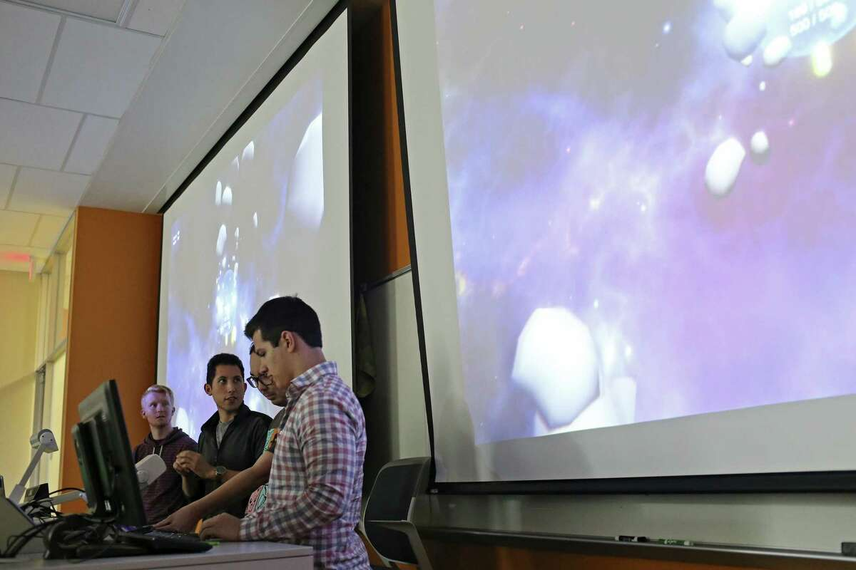 Andrew Sanetra, 21, second from left, explains a video game designed for U.S. Army veteran, Anne Robinson, 48, during a presentation between fellow students at the University of Texas at San Antonio main campus on Dec. 14. With Sanetra are from left, Trase Westbrook, 21, Clifford Hill, 28, and Edward Mondragon, 23. Robinson is a quadriplegic.