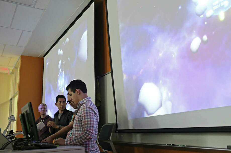Andrew Sanetra, 21, second from left, explains a video game designed for U.S. Army veteran, Anne Robinson, 48, during a presentation between fellow students at the University of Texas at San Antonio main campus on Dec. 14. With Sanetra are from left, Trase Westbrook, 21, Clifford Hill, 28, and Edward Mondragon, 23. Robinson is a quadriplegic. Photo: JERRY LARA /San Antonio Express-News / © 2017 San Antonio Express-News