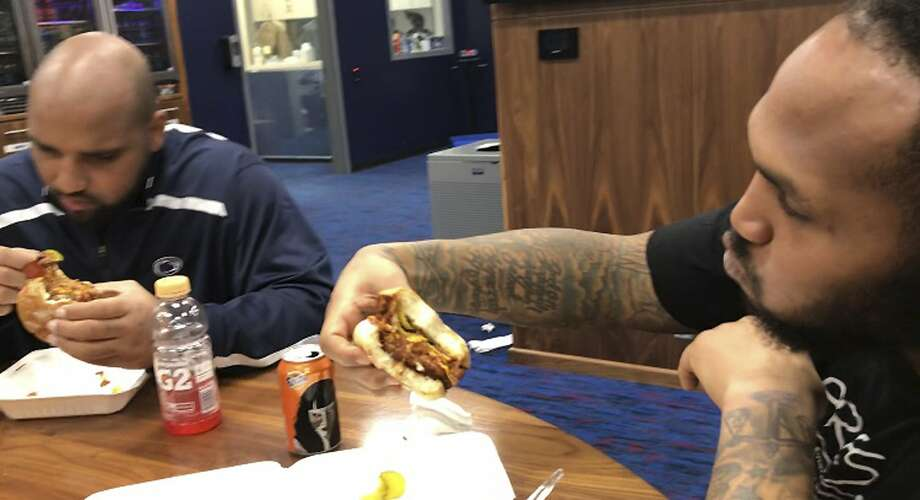 Tennessee Titans defensive lineman DaQuan Jones ( left) and defensive end Jurrell Casey eat vegetarian cheeseburgers provided by chef Charity Morgan. Photo: Teresa Walker, Associated Press