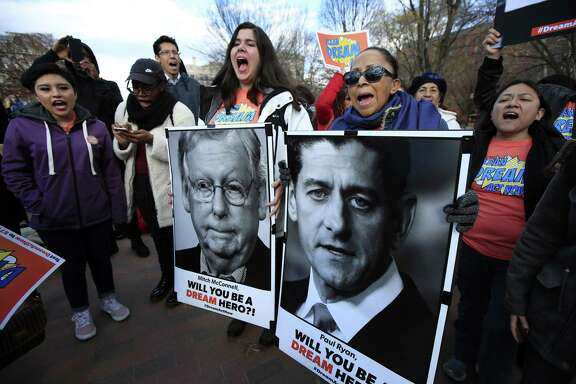 Amanda Bayer, left holding banner, and Marisol Maqueda, right with banner, from Mexico whose daughter Maria Torres also from Mexico City is a DACA recipient finishing her masters degree from Arizona, join a rally outside the White House in Washington, Thursday, Dec. 7, 2017. (AP Photo/Manuel Balce Ceneta).