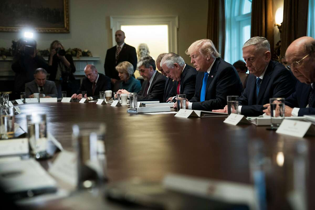 President Donald Trump and his Cabinet bow their heads for a prayer Wednesday during a meeting in which they celebrated the passage of the GOP tax bill. MUST CREDIT: Washington Post photo by Jabin Botsford