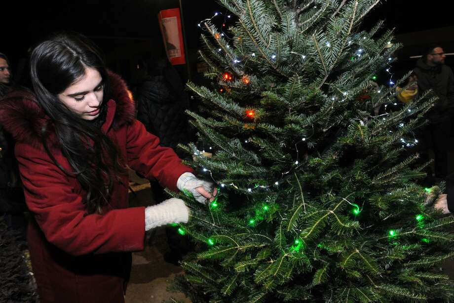 Jazmarie Melendez, sister of Jayson Negron, helps decorate a Christmas tree set up near the spot on Fairfield Ave. where Negron was shot a killed by Bridgeport Police last May, seen here Dec. 20, 2017. Photo: Ned Gerard / Hearst Connecticut Media / Connecticut Post