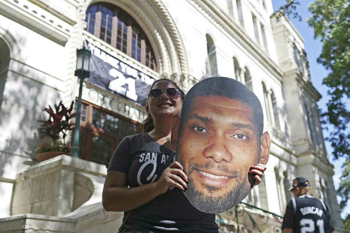 San Antonio Spurs fan Hanna Castillo gets her picture taken near a banner honoring Tim Duncan in front of City Hall, July 21, 2016. Duncan announced his retirement from the Spurs on July 11. He played for the Spurs for 19 seasons. Mayor Ivy Taylor officially declared July 21 as Tim Duncan Day, reflecting his jersey number.
