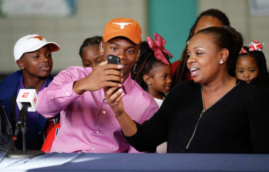 Anthony Cook of Lamar, one of the state's top football recruits, with his mother, Tomeka McKinney, moments after he made his announcement that he will be attending The Univeristy of Texas during a live televised announcement at Lamar High School, Wednesday, Dec. 20, 2017, in Houston.   ( Karen Warren / Houston Chronicle ) Photo: Karen Warren, Staff / © 2017 Houston Chronicle