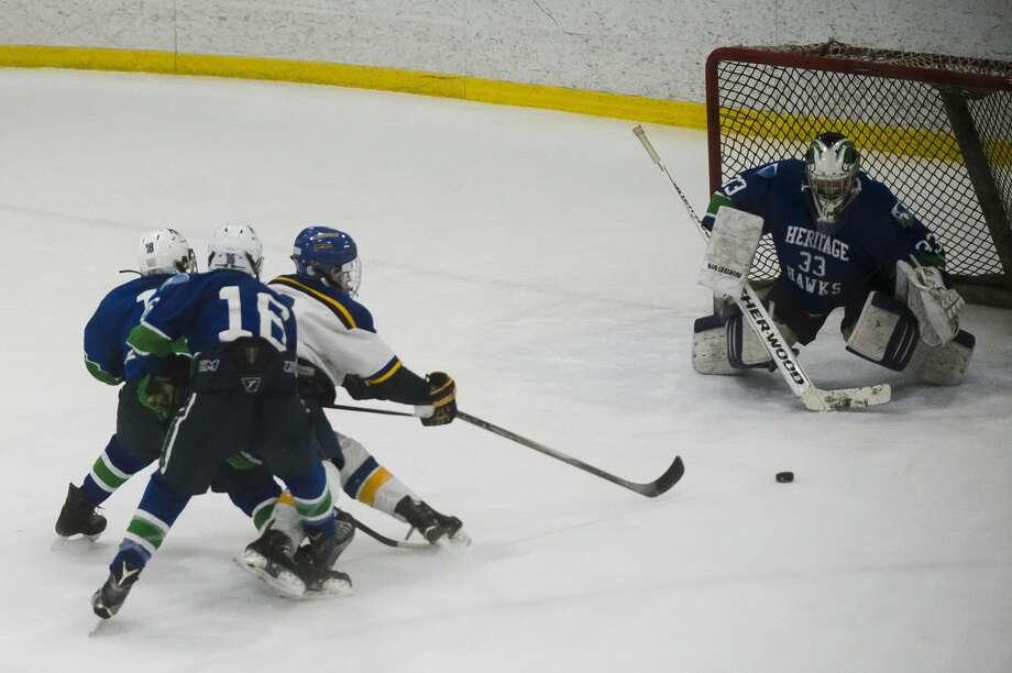 Midland sophomore Matthew Babinski takes a shot on goal during the Chemics' game against Saginaw Heritage on Wednesday, Dec. 20, 2017 at Midland Civic Arena. (Katy Kildee/kkildee@mdn.net) Photo: (Katy Kildee/kkildee@mdn.net)