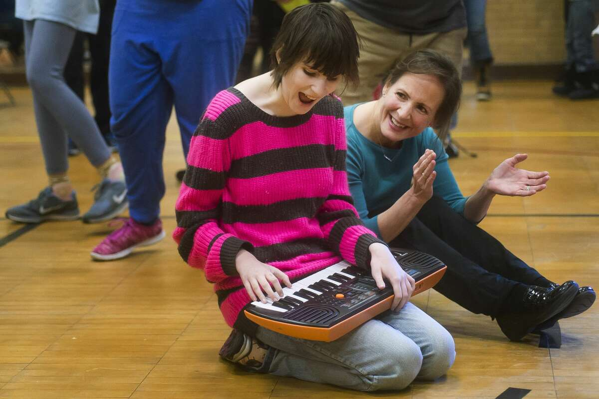 Delaney McKimmy of Midland plays the keyboard as Barbara Jacques of Midland claps along during the All Music is Power concert on Tuesday, Dec. 19, 2017 at the Midland County Educational Service Agency. All Music is Power provides concerts for children with special needs to encourage movement and expression. (Katy Kildee/kkildee@mdn.net)