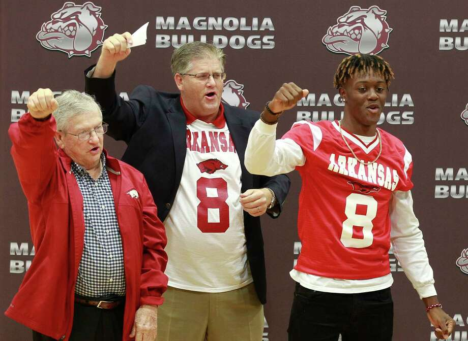 Magnolia's Michael Woods, right, chants 'Woo Pig Sooie' beside Chris Gunnell, center, and  Chris Price, a member of the 1964 Arkansas National Championship team, after Woods signed a National Letter of Intent to play football for Arkansas during a ceremony at Magnolia High School, Wednesday, Dec. 20, 2017, in Magnolia. Photo: Jason Fochtman, Staff Photographer / © 2017 Houston Chronicle