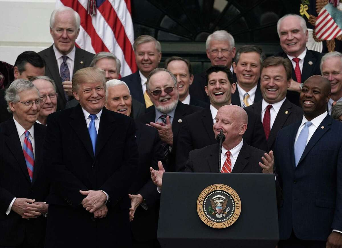 WASHINGTON, DC - DECEMBER 20: Chairman of House Ways and Means Committee Rep. Kevin Brady (R-TX) (C) as President Donald Trump (3rd L) looks on during an event to celebrate Congress passing the Tax Cuts and Jobs Act with Republican members of the House and Senate on the South Lawn of the White House December 20, 2017 in Washington, DC. The tax bill is the first major legislative victory for the GOP-controlled Congress and Trump since he took office almost one year ago. (Photo by Alex Wong/Getty Images)