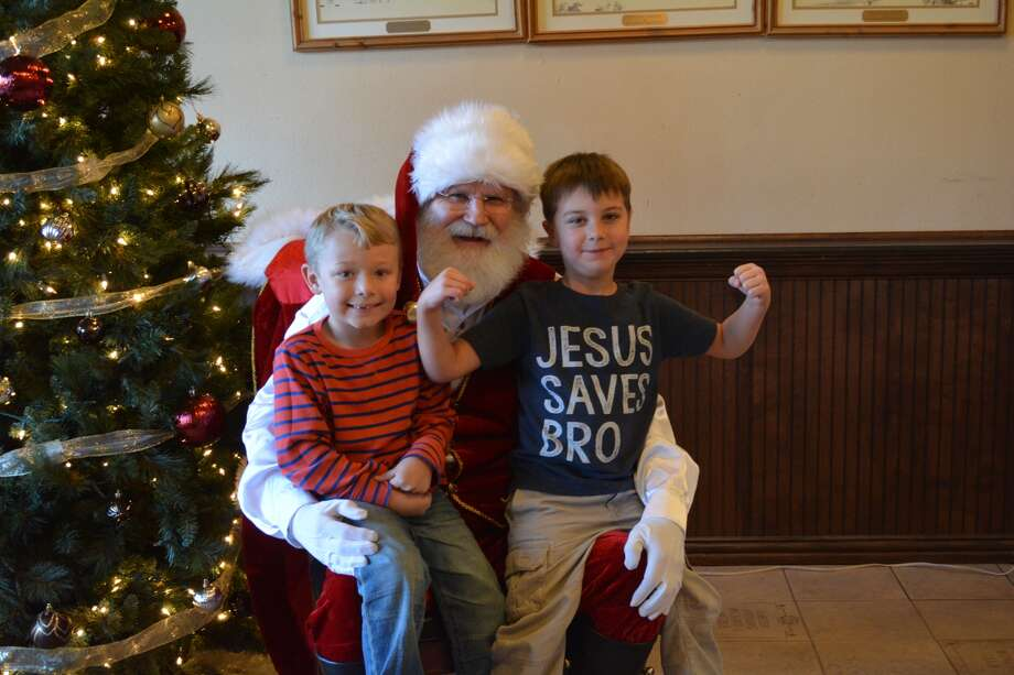 Sawyer Snyder and Gus Boedeker tell Santa what they want for Christmas during Plainview Main Street's Soup, Santa and Sopapillas event.