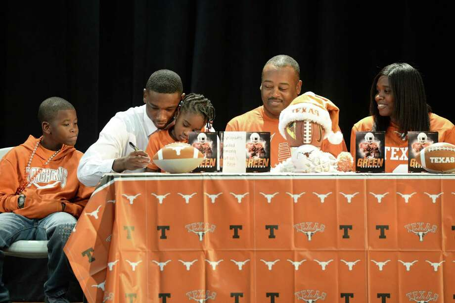With family looking on Wednesday, Heights cornerback Jalen Green signs on the dotted line to play football at the University of Texas. Defensive backs appeared to be the strength of a strong recruiting class for UT coach Tom Herman. Photo: Craig Moseley, Staff / ©2017 Houston Chronicle