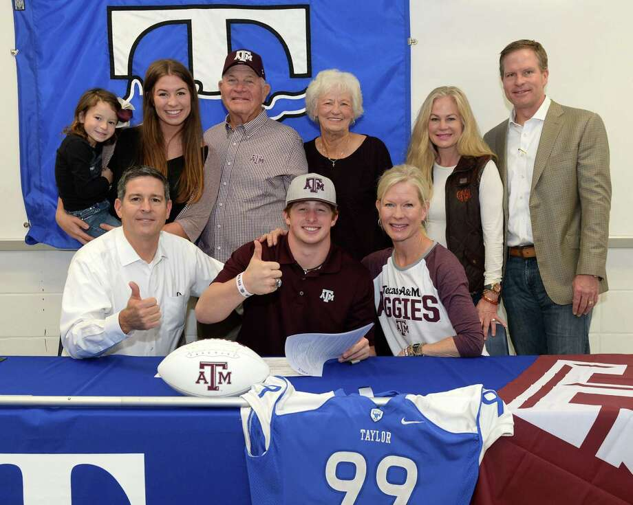 Max Wright, a defensive end from Katy Taylor, is surrounded by his family after signing a commitment to play football at Texas A&M on Wednesday. Photo: Craig Moseley, Staff / ©2017 Houston Chronicle