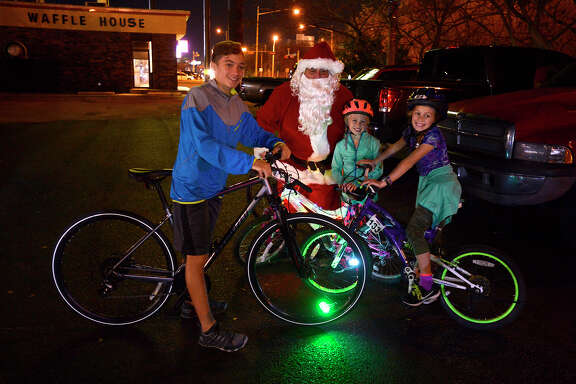 Major, Rain and Ivy Mae Hargraves before the start of a Christmas-themed bike ride at Bicycle Sports on Wednesday night. The group rode their festive bikes through Old Town and West End neighborhoods looking at Christmas lights.  Photo taken Wednesday 12/20/17 Ryan Pelham/The Enterprise