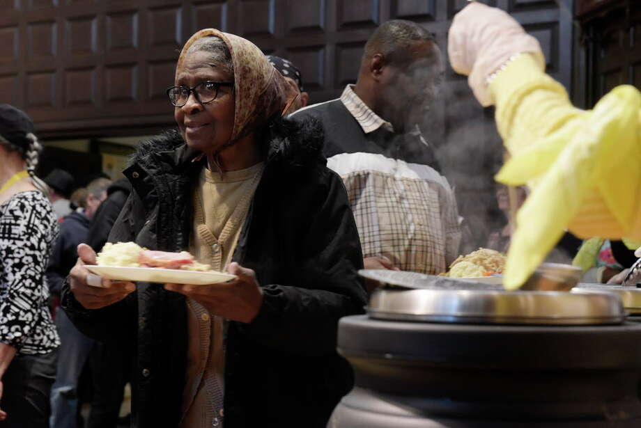 Mae Etta Seabrooks of Albany makes her way to a table after getting a plate of food at the 48th Annual Equinox Thanksgiving Community Dinner on Thursday, Nov. 23, 2017, in Albany, N.Y. Many charities and churches are worried that tax changes could curb charitable giving.  (Paul Buckowski / Times Union) Photo: PAUL BUCKOWSKI / 20042142A
