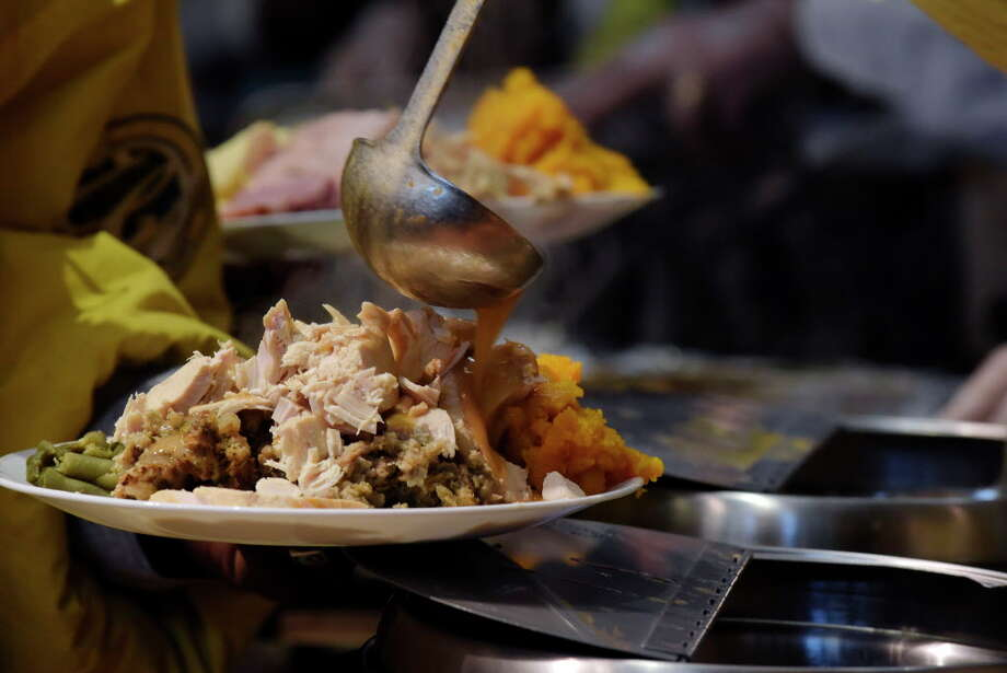 Gravy is poured onto a plate of food at the 48th Annual Equinox Thanksgiving Community Dinner on Thursday, Nov. 23, 2017, in Albany, N.Y. (Paul Buckowski / Times Union) Photo: PAUL BUCKOWSKI / 20042142A