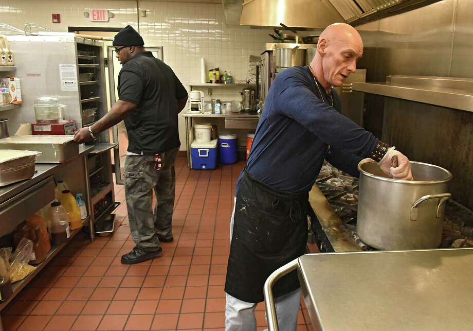 Dining Services team members Kory Baskin, left, and John Lobdell prepare food for dinner at the City Mission of Schenectady on Thursday, Dec. 7, 2017 in Schenectady, N.Y. The men are all former participants of the long-term residential Bridges to Freedom program. (Lori Van Buren / Times Union) Photo: Lori Van Buren / 20042337A