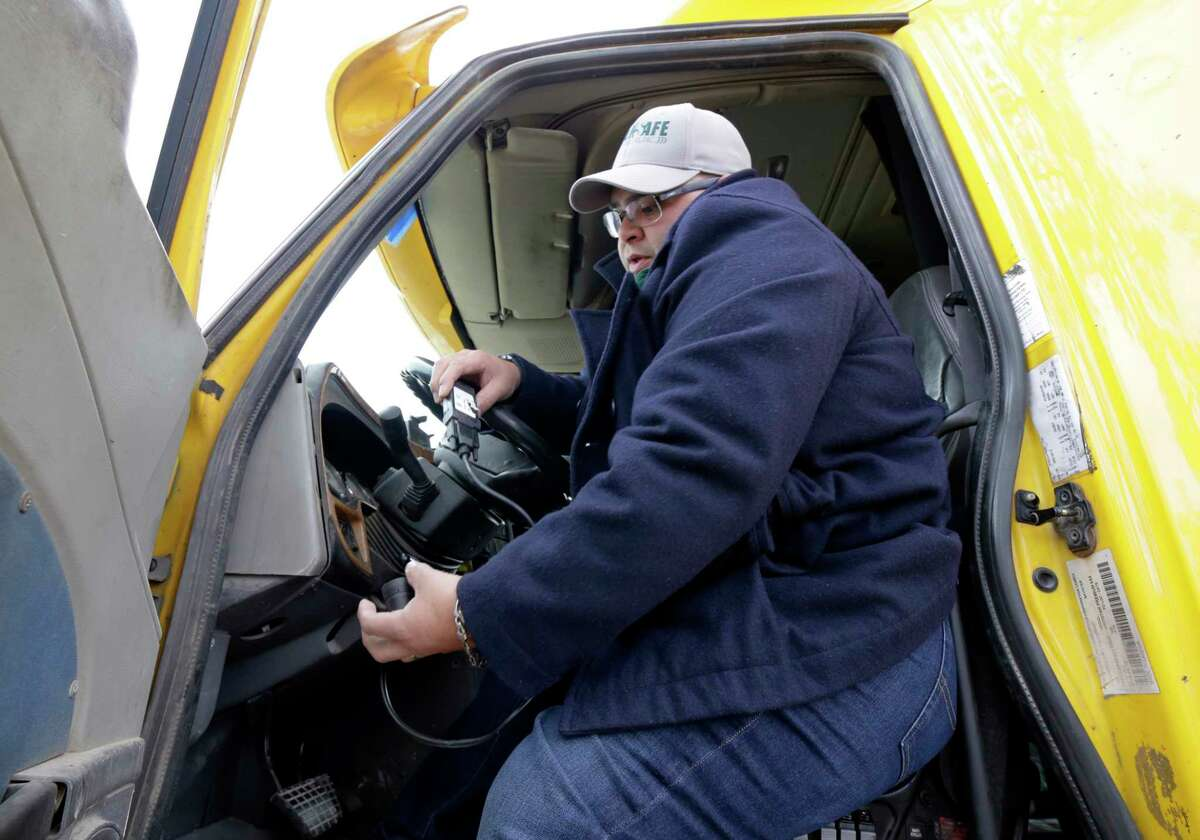 Jurgen Morales installs an electronic logging device that tracks driver hours into the cab of a semi-truck at Transafe in Houston, TX, Dec. 15, 2017. A pigtail plug device connects to a terminal under the dash board and a tablet provides information from the device to the driver. (Michael Wyke / For the Chronicle)