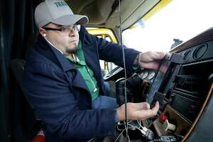 Jurgen Morales attaches a tablet to the dash as he installs an electronic logging device that tracks driver hours into the cab of a semi-truck at Transafe in Houston, TX, Dec. 15, 2017. A pigtail plug device connects to a terminal under the dash board and the tablet  provides information from the device to the driver. (Michael Wyke / For the  Chronicle)