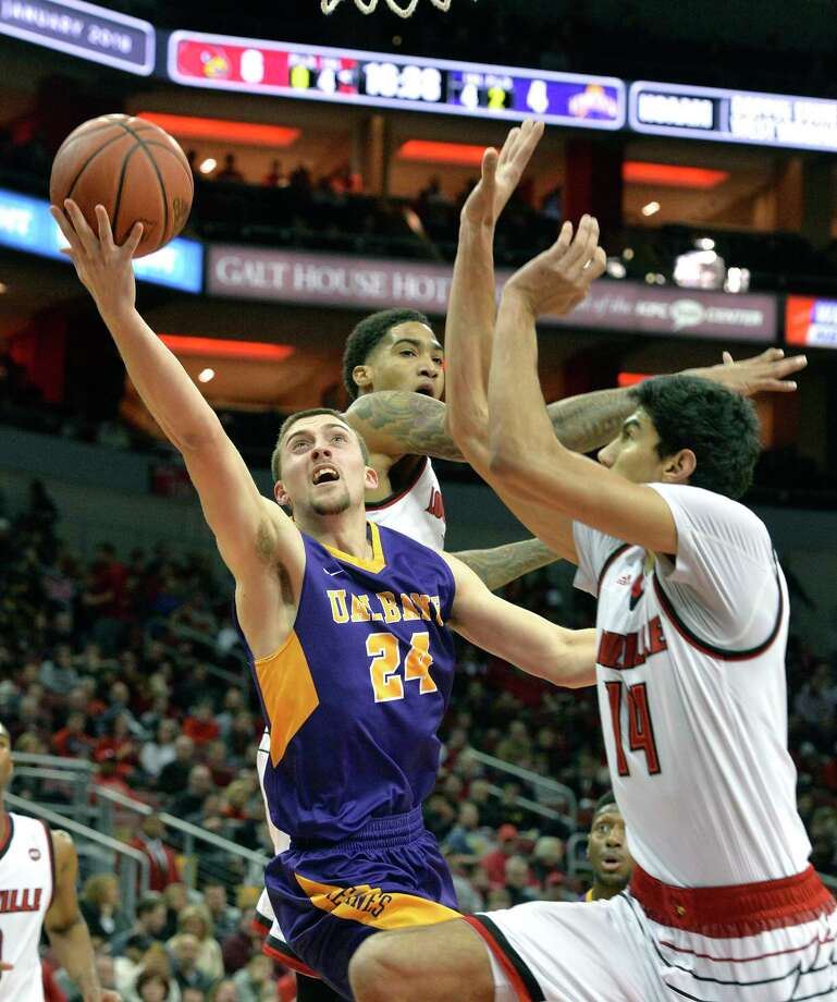 Albany guard Joe Cremo (24) attempts a layup past the defense of Louisville forward Ray Spalding (13), and forward Anas Mahmoud (14) during the first half of an NCAA college basketball game, Wednesday, Dec. 20, 2017, in Louisville, Ky. (AP Photo/Timothy D. Easley) Photo: Timothy D. Easley / FR43398 AP