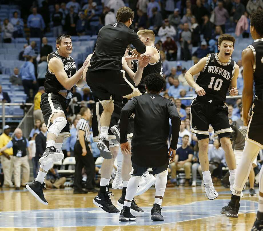 Wofford players including Fletcher Magee (far left) and Nathan Hoover (10) celebrate after the Terriers beat fifth-ranked North Carolina 79-75. Photo: Ellen Ozier, Associated Press