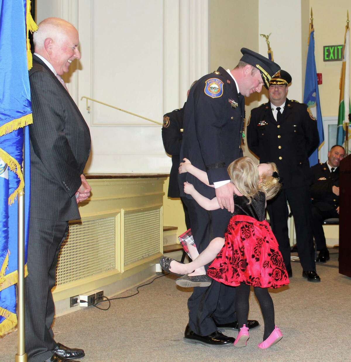 Captain Ryan Paulsson hugs his two daughers at the police promotion ceremon in Westport Town Hall on Dec. 14.