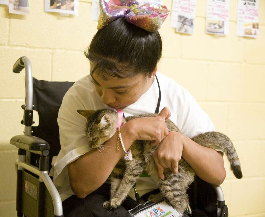 April Cadena is a volunteer at Laredo Animal Protective Society, a local no-kill shelter. Her mother Mabel says the shelter has allowed her to feel like part of the community, which has been difficult because of her disability. Photo: Courtesy