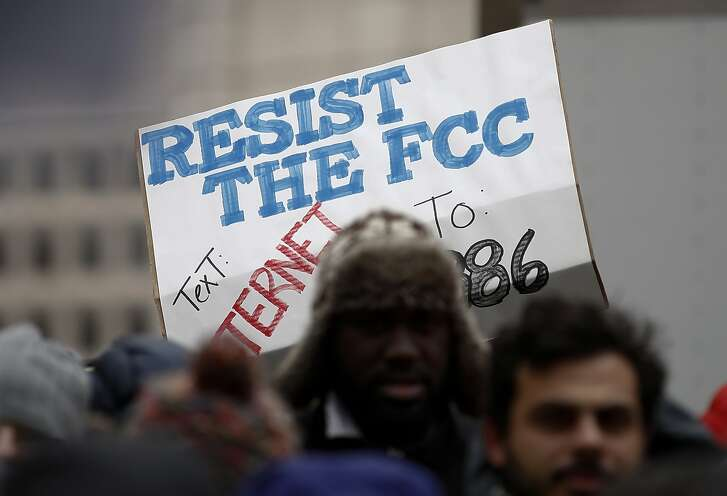 """A protester holds a sign that reads """"Resist the FCC Text: INTERNET To: 52886"""" at the Federal Communications Commission (FCC), in Washington, Thursday, Dec. 14, 2017. The FCC voted to eliminate net-neutrality protections for the internet. (AP Photo/Carolyn Kaster)"""