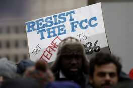 "A protester holds a sign that reads ""Resist the FCC Text: INTERNET To: 52886"" at the Federal Communications Commission (FCC), in Washington, Thursday, Dec. 14, 2017. The FCC voted to eliminate net-neutrality protections for the internet. (AP Photo/Carolyn Kaster)"