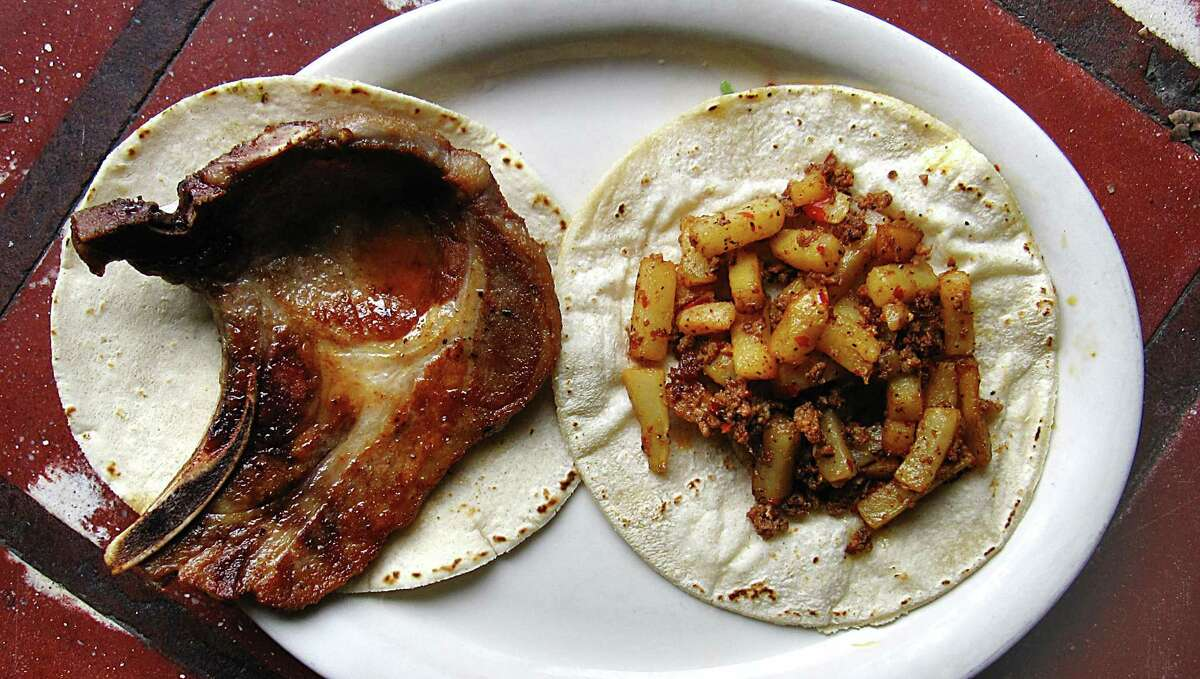 Pork chop taco, left, and a chorizo and potatoes taco, both on handmade corn tortillas, from Tacos El Rey.