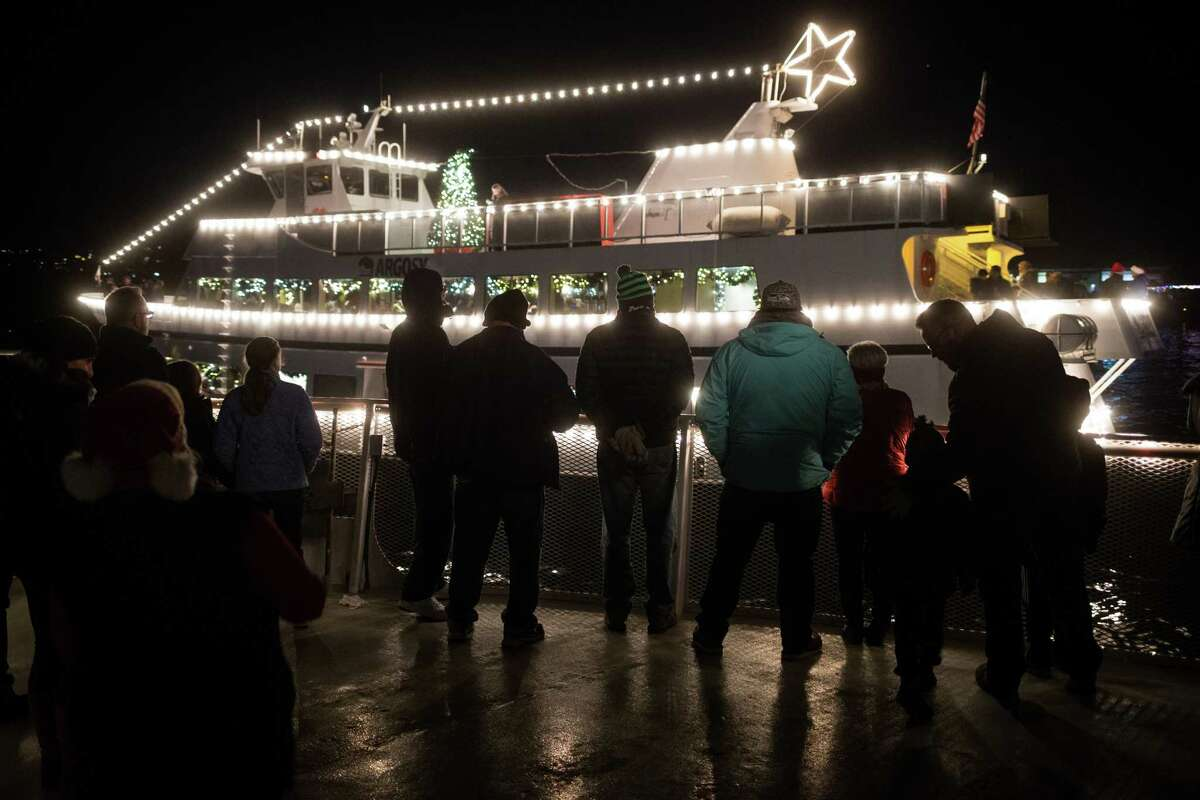 Passengers listen from the follow boat to carols playing over loud speakers aboard the Christmas Ship on Lake Washington on Wednesday, Dec. 20, 2017.