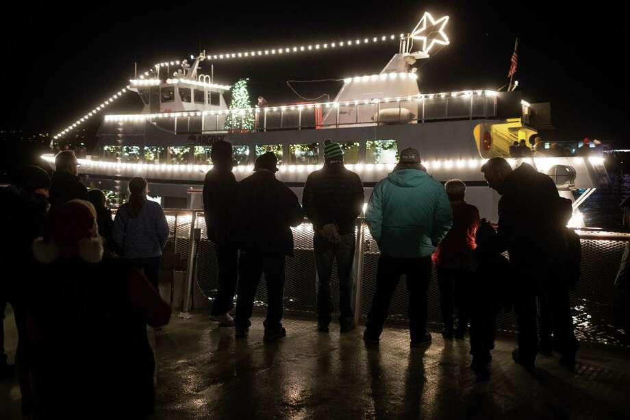 Passengers listen from the follow boat to carols playing over loud speakers aboard the Christmas Ship on Lake Washington on Wednesday, Dec. 20, 2017. Photo: GRANT HINDSLEY, SEATTLEPI.COM / SEATTLEPI.COM