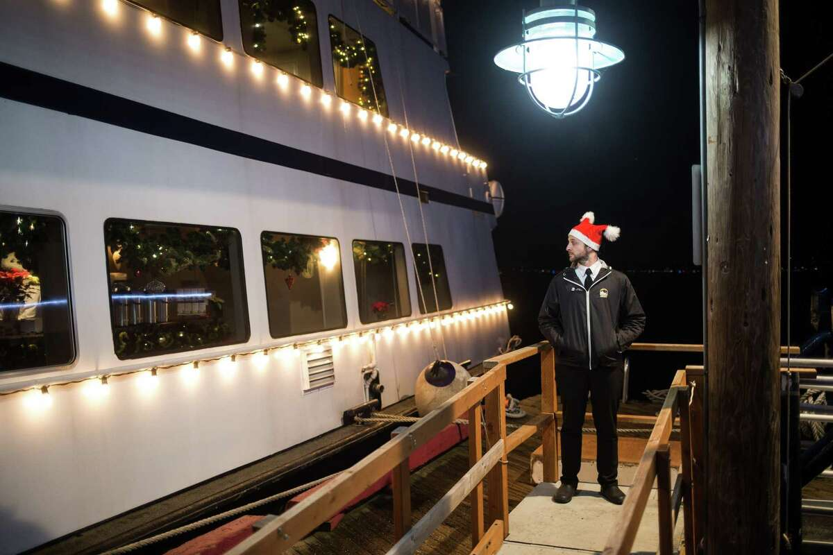 Argosy staff leads patrons to their respective boats before a Christmas cruise around Lake Washington on Wednesday, Dec. 20, 2017.