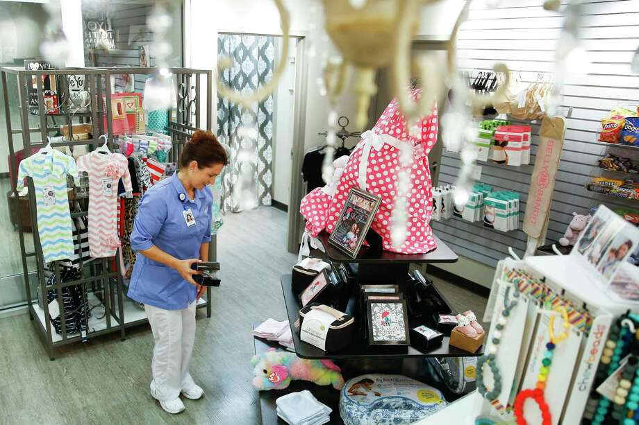 Volunteer Ronel Van der Walt organizes display items, including birthing gowns, at Memorial Hermann Katy Hospital's Honeysuckle Boutique. Photo: Michael Ciaglo, Houston Chronicle / Michael Ciaglo