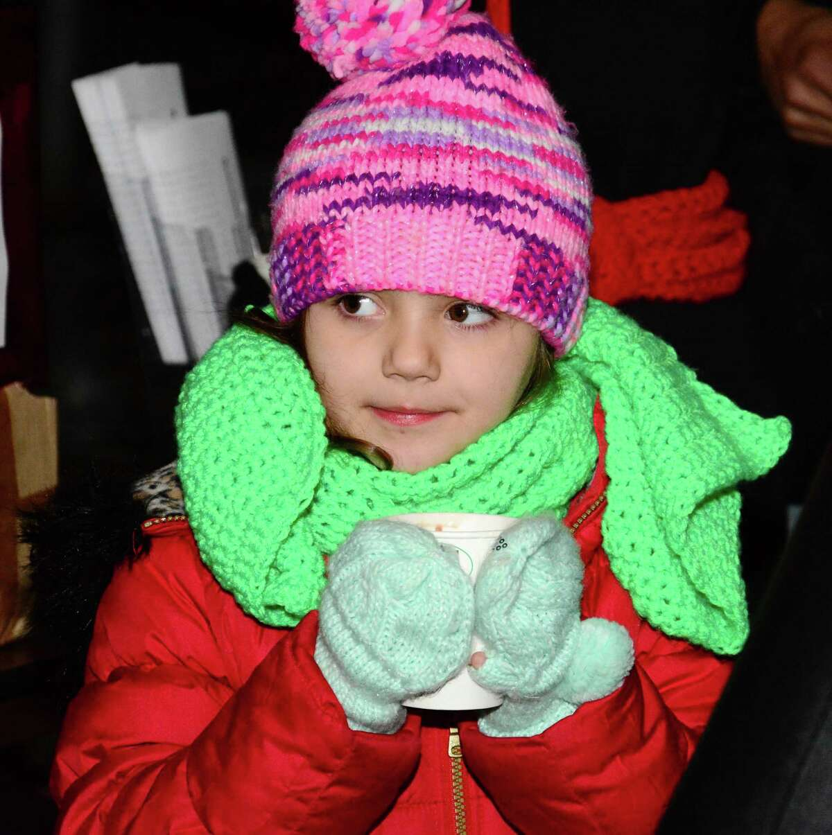 Above, Layla Reidy, 6, holds a warm cup of hot cocoa at New Milford's Annual Carol Sing on the Green, Monday. Christie Blum from Brookfield, Billy Schulze, 4, and Stephanie Schultze, both from New Milford, take a selfie while they wait for the hayride to begin. Right, Santa Claus listens to Leila Nararrete, 7, from New Milford.