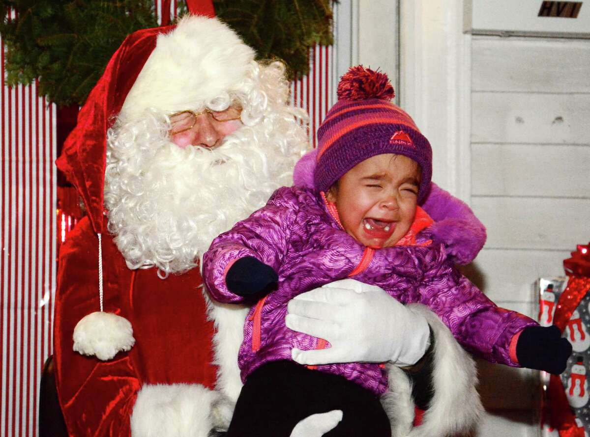 Santa Claus gets a picture with Larissa Barrows from New Milford during New Milfords Annual Christmas Carol Sing on the green on Monday, December 18, 2018.