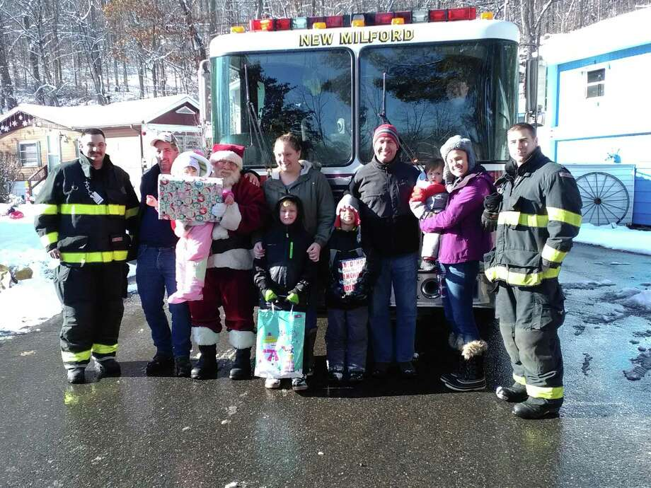 Water Witch Hose Company No. 2 held its annual Santa Express on Dec. 10 in New Milford. Two teams of firefighters, accompanied by Santa Claus, delivered presents to children at 40 different stops in town during the day. One of the stops was Eden Lane in Candle Hill Mobile Home Community. Above, from left, are firefigher Seth Castagna, Wes Morse, Johnna Morse, 2, Santa Claus, Michelle Svendberg, Liam Servoss, 6, Dave and Melissa McVeigh, Ryan McVeigh, 6, Colton McVeigh,18 months, and firefighter Ed Powers. Driving the truck is firefighter Jeff Emmons. Photo: Emily M. Olson / Hearst Connecticut Media