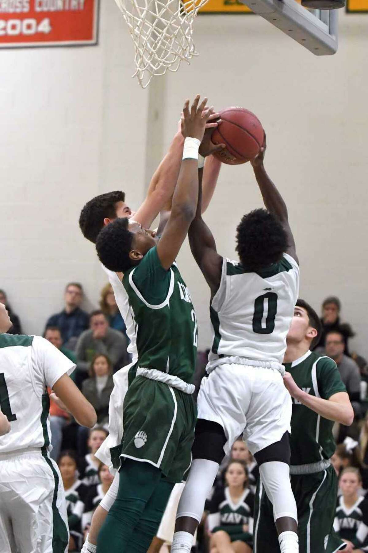 From left, New Milford's Christopher Gesauldi, Norwalk's Zyaire Sellers, and New Milford's Malik Proctor vie for the ball Monday night in New Milford.