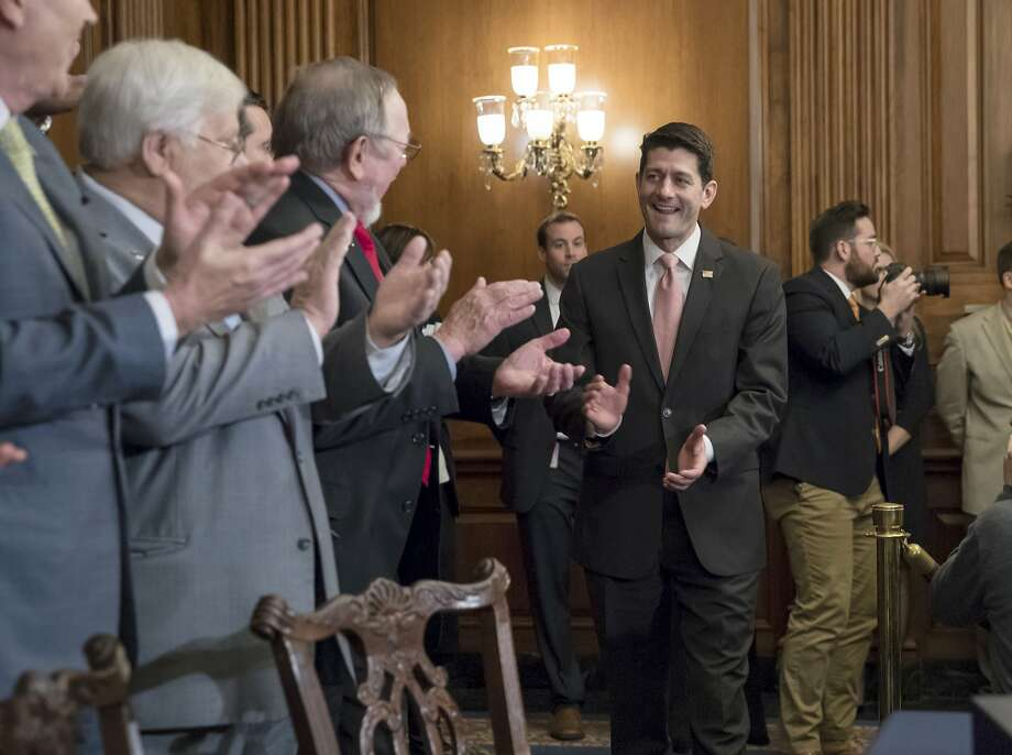 Speaker of the House Paul Ryan, R-Wis., is welcomed by fellow Republicans as he arrives to sign the final version of the GOP tax bill during an enrollment ceremony at the Capitol in Washington, Thursday, Dec. 21, 2017. (AP Photo/J. Scott Applewhite) Photo: J. Scott Applewhite, Associated Press