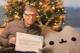 Bill Gates poses with the Pusheen and his letter to Megan Cummins.