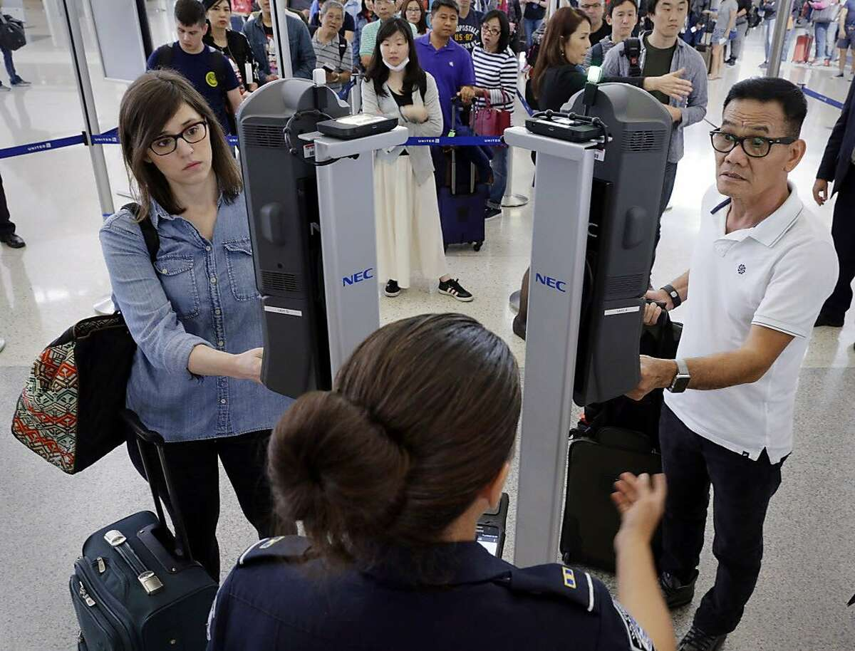 U.S. Customs and Border Protection officer Charmaine Guillory (center bottom) stands by to assist passengers as they use the new face recognition kiosks being tested at United Airlines gate E7 before boarding a flight to Tokyo at Bush Intercontinental Airport in Houston, When everything checks out, passengers spend less than 10 seconds at the kiosk before proceeding with the standard boarding activities. (Michael Wyke / For the Chronicle)