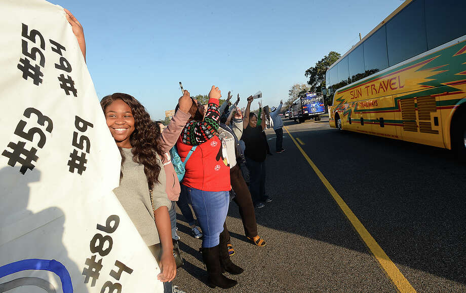 Students, including Kennedy Queen (left), fans and community members line the roadway outside West Orange - Stark High School to cheer on the Mustangs as they head to Arlington for their state title game Thursday morning. The Mustangs will face Pleasant Grove at 3 p.m. Friday. Photo taken Thursday, December 21, 2017 Kim Brent/The Enterprise Photo: Kim Brent/Beaumont Enterprise
